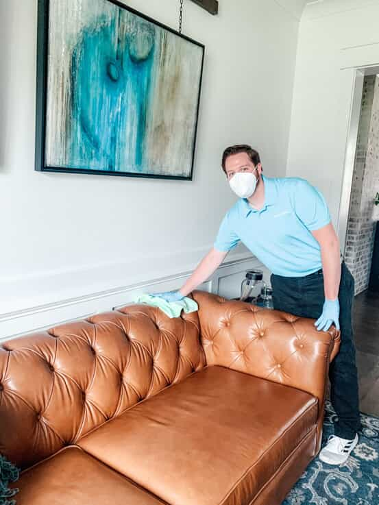 Merry Maids housekeeper wiping down a leather couch