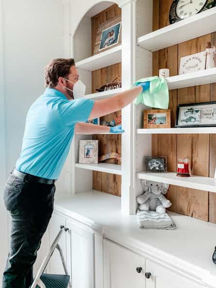 cleaning professional deep cleaning a bedroom by dusting high shelves with a step stool