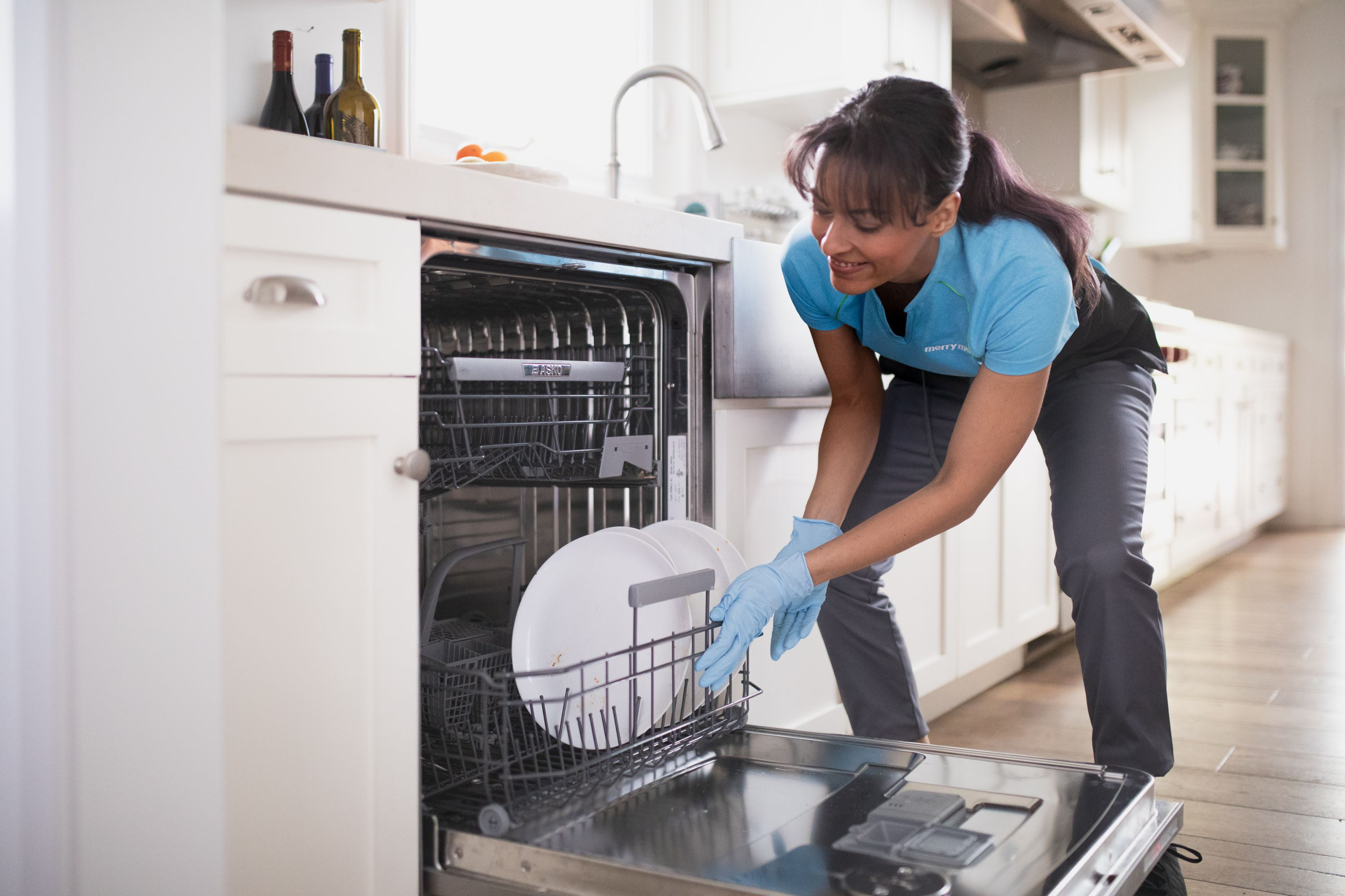 Merry Maids team member loading a dishwasher