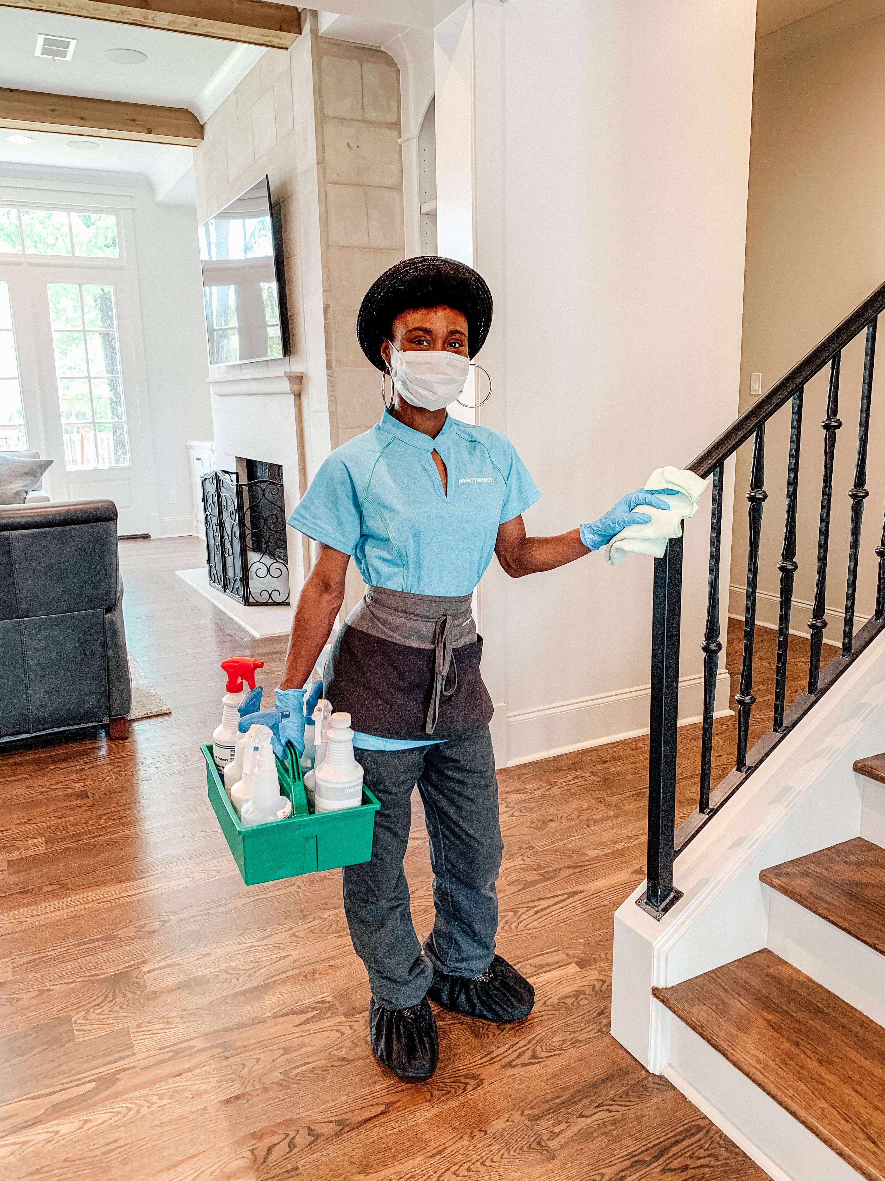 Merry Maids cleaning professional providing enhanced disinfection on a stairway railing
