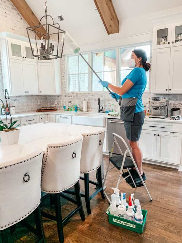 professional maid cleaning a hanging lamp above a kitchen table