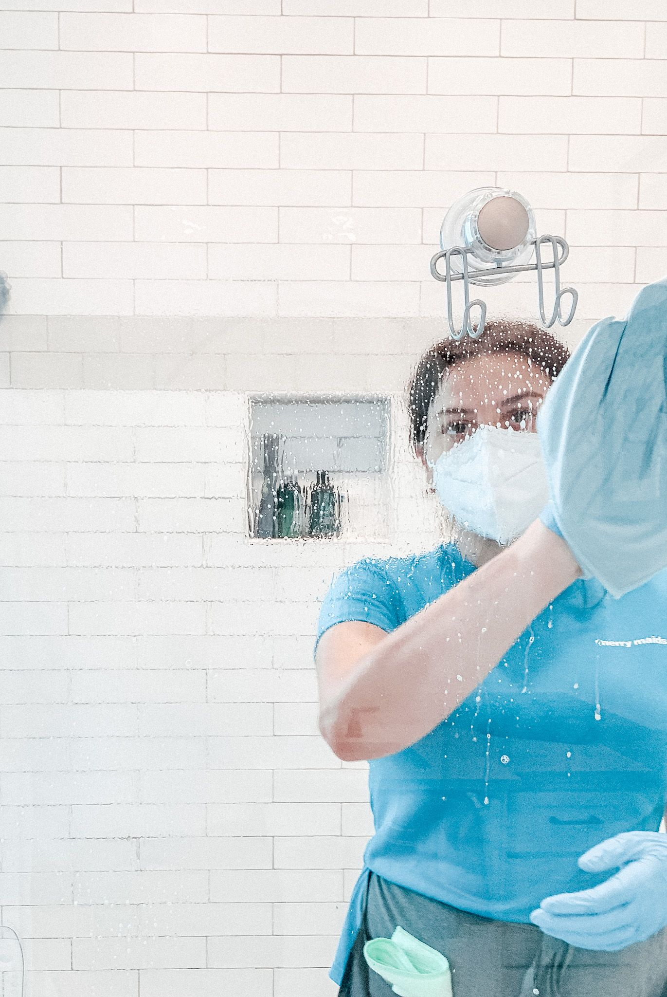 Merry Maids team member wearing PPE and disinfecting glass inside a bathroom
