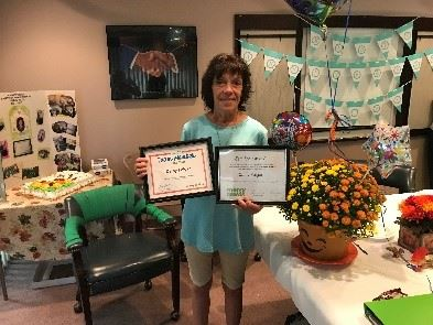 Cathy Folger, Merry Maids employee holding awards