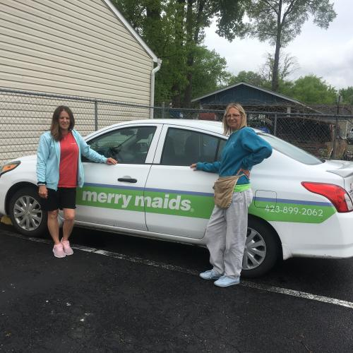 Two Women in Front of the Merry Maids Car