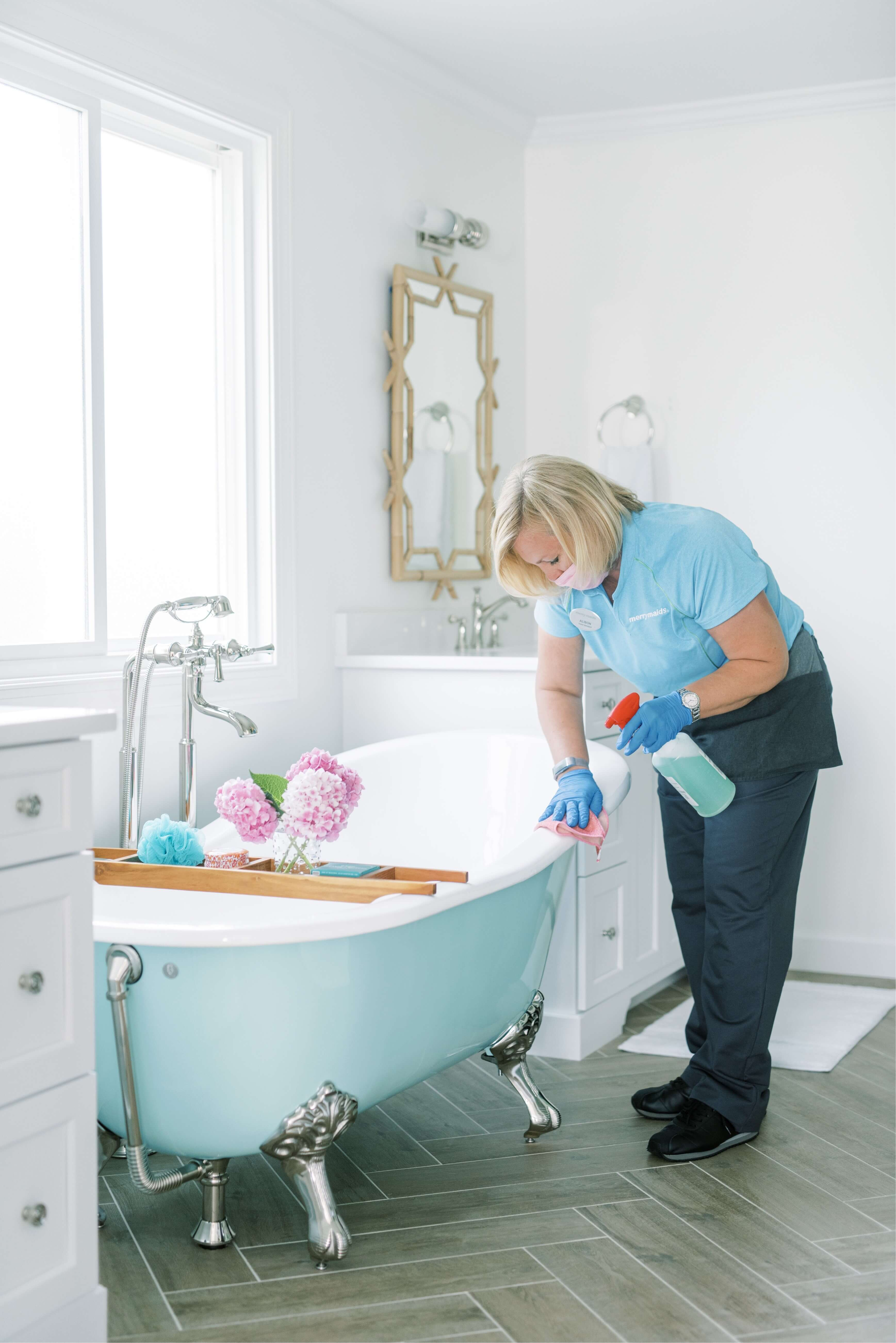 Merry Maids team member cleaning bathtub