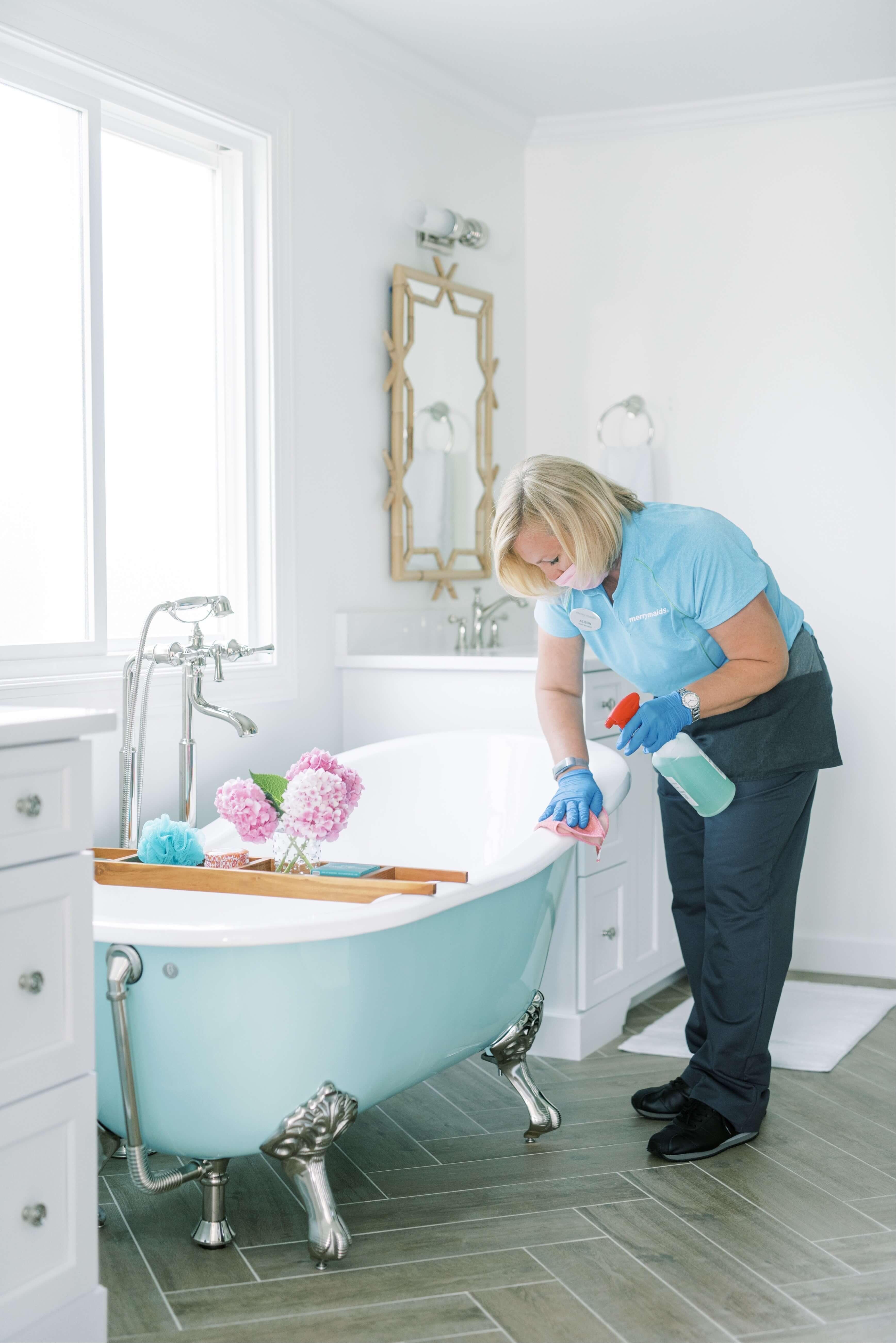 Merry Maids team member cleaning bathtub