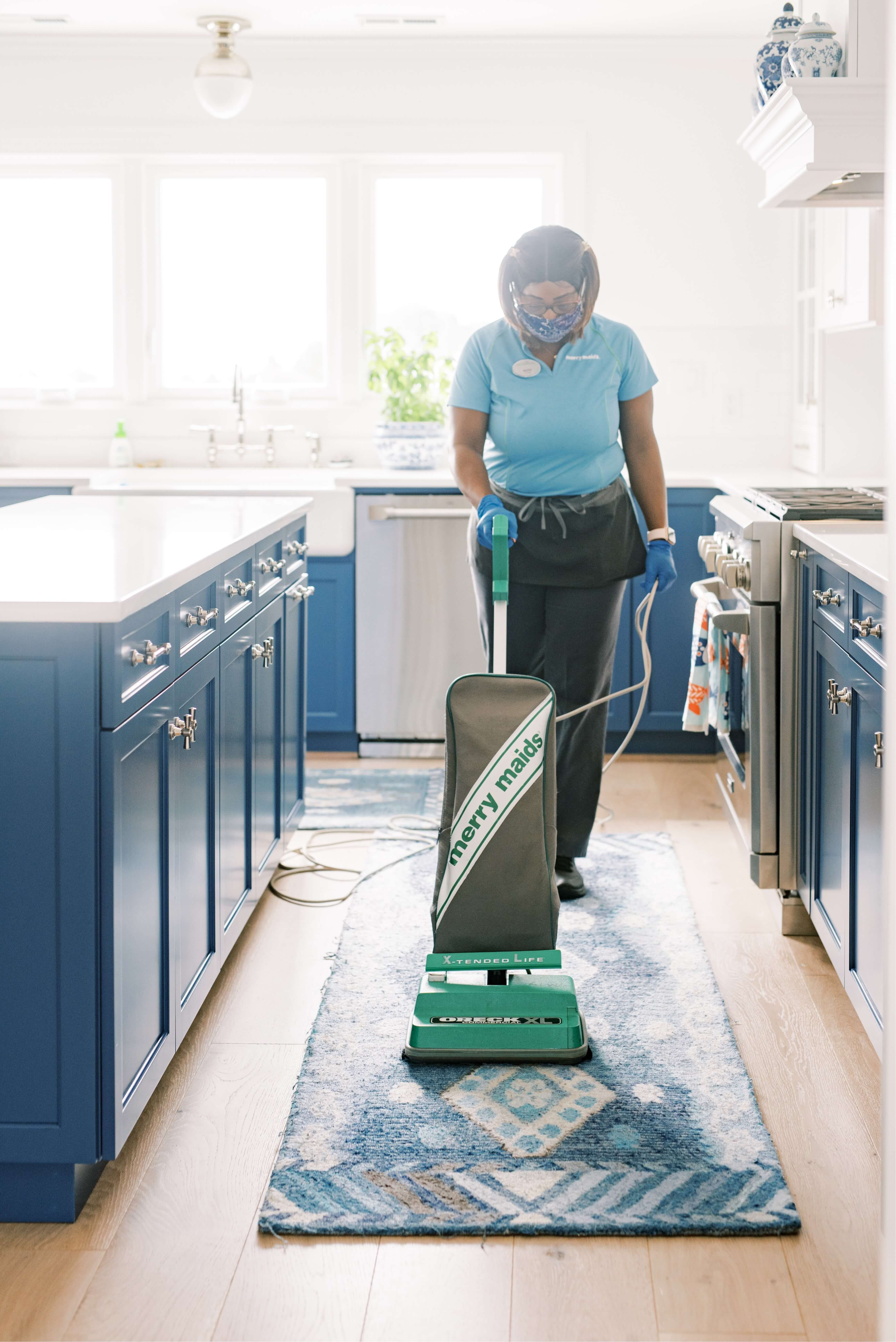 Merry Maids team member vacuuming in kitchen