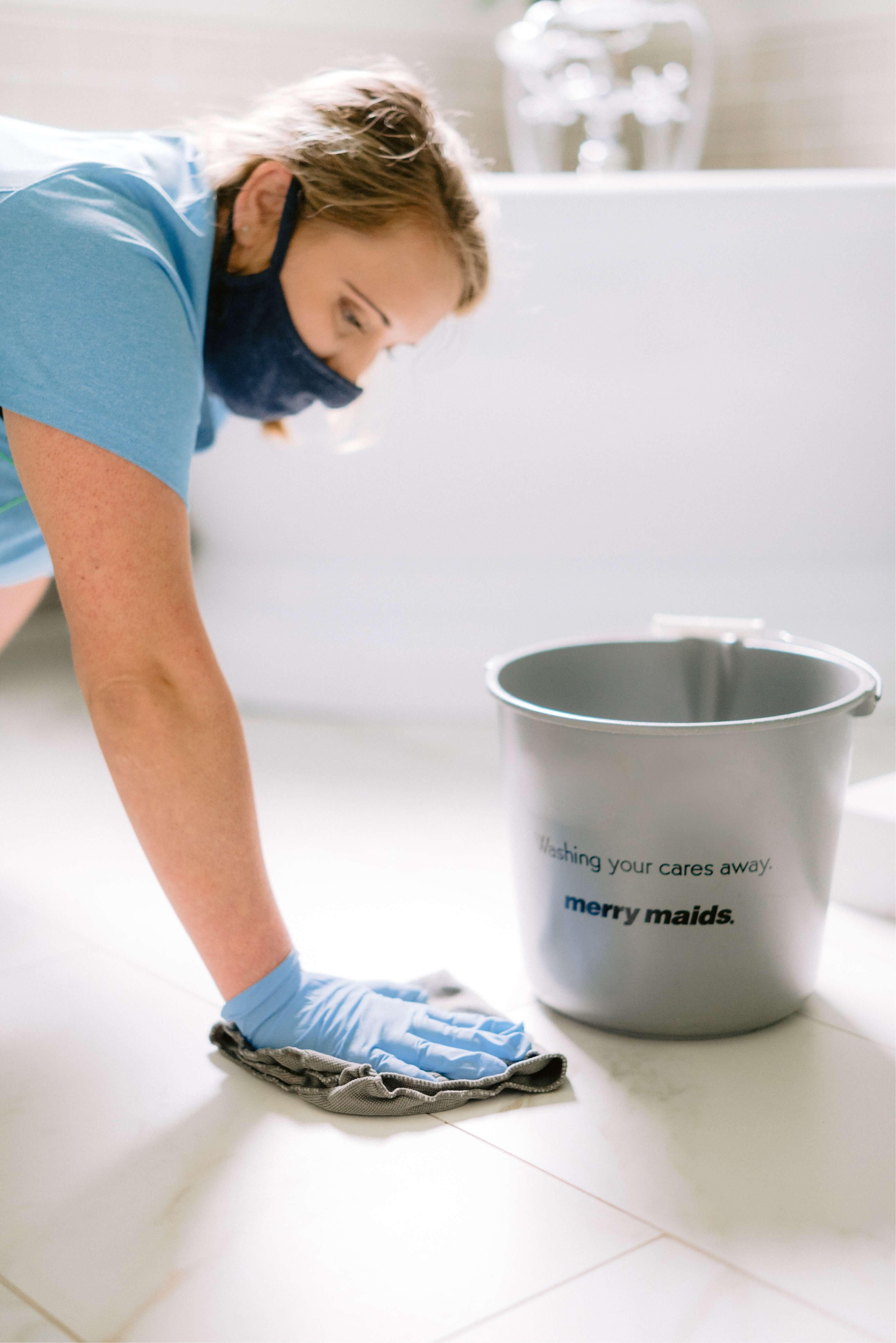 Merry Maids team member scrubbing tile floors