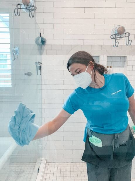 maid cleaning and disinfecting a bathroom