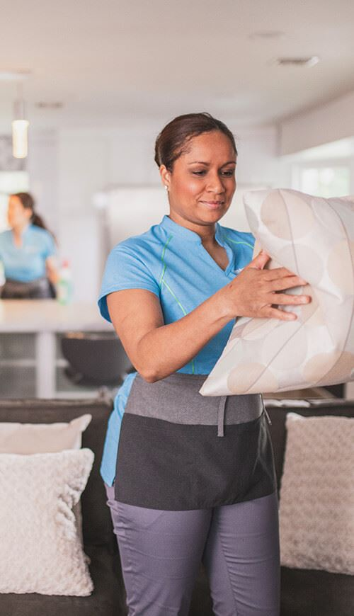 house maid fluffing a pillow from a couch