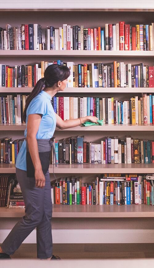 maid deep cleaning a room with bookshelves