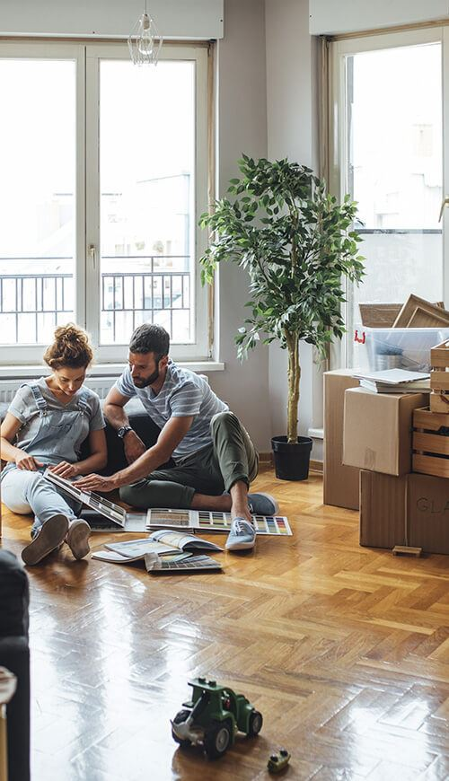 couple sitting on the floor of a clean apartment surrounded by boxes